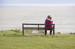 Frau, die auf einer Bank sitzt Stockfoto