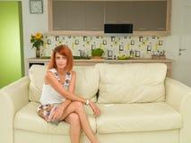 Frau, die auf einer Couch, entspannt sitzt Stockfotografie