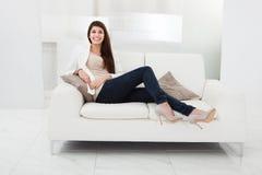 Frau, die auf einer Couch sitzt Lizenzfreie Stockfotos