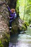 Frau, die auf einer Gebirgswand klettert Lizenzfreie Stockfotografie