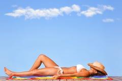 Frau, die auf einer hölzernen Plattform ein Sonnenbad nimmt Lizenzfreie Stockbilder