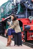 Frau, die auf einer Hauptverkehsstraße und Gebrauch das Telefon sitzt Stockbilder