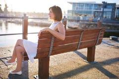 Frau, die auf einer Holzbank genießt das warme Sonnenlicht sitzt stockbild