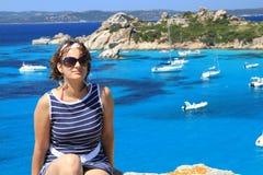 Frau, die auf einer Klippe sitzt Sardinien, Italien Stockbilder