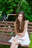 Frau, die auf einer Parkbank mit ihrem Buch sitzt Stockfoto