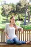 Frau, die auf einer Parkbank sich entspannt Stockbilder