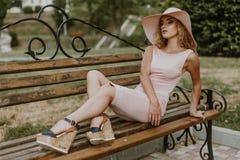 Frau, die auf einer Parkbank sitzt Stockfotografie