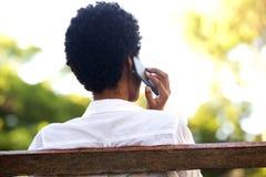 Frau, die auf einer Parkbank sitzt und am Handy spricht Stockbilder