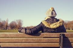 Frau, die auf einer Parkbank stillsteht Lizenzfreie Stockfotos