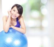 Frau, die auf einer pilates Kugel sich lehnt Stockbild