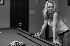 Frau, die auf einer Pooltabelle sich lehnt Lizenzfreies Stockfoto