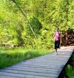 Frau, die auf einer Promenade im Wald rüttelt Stockfotos