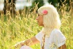 Frau, die auf einer Sommerwiese sitzt und weg schaut Stockbild