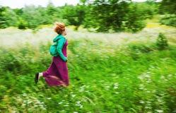 Frau, die auf einer Wiese läuft Stockfotos