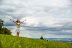Frau, die auf einer Wiese mit ihren Händen angehoben zum Himmel steht Stockfotografie