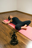 Frau, die auf einer Yoga-Matte - Vertikale liegt Stockfotografie