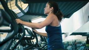 Frau, die auf elliptischer Maschine an der Turnhalle ausarbeitet stock video