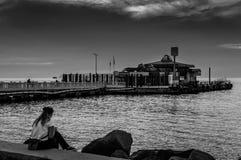 Frau, die auf Fährhafen am Abend wartet Stockfoto