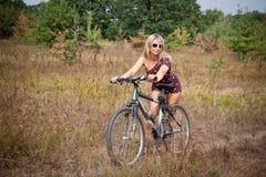 Frau, die auf Fahrrad aufwirft Lizenzfreie Stockfotografie