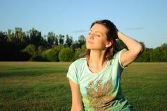Frau, die auf Feld sich entspannt Stockfoto