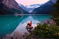 Frau, die auf Felsen in Lake Louise bei Sonnenuntergang sitzt Stockfotos