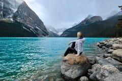 Frau, die auf Felsen in Lake Louise sitzt und die Ansicht von Victoria Glacier genießt Stockfotografie