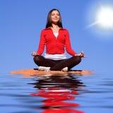 Frau, die auf Felsen meditiert Stockbilder