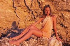 Frau, die auf Felsen sich entspannt Lizenzfreies Stockfoto