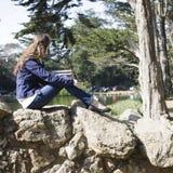 Frau, die auf Felsen sitzt lizenzfreie stockfotos