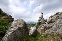Frau, die auf Felsen sitzt stockbild