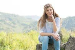 Frau, die auf Felsen sitzt Stockfoto