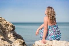 Frau, die auf Felsen sitzt Stockfotos