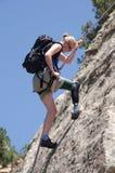 Frau, die auf Felsengesicht mit dem prothetischen Fahrwerkbein sichert. Lizenzfreie Stockbilder