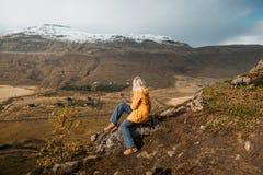 Frau, die auf felsiger Klippe sitzt und betrachtet, überraschend nordische Landschaft, Island Reise und Natur lizenzfreie stockbilder