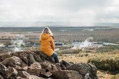 Frau, die auf felsiger Klippe sitzt und betrachtet, überraschend nordische Landschaft, Island Reise und Natur stockfotos