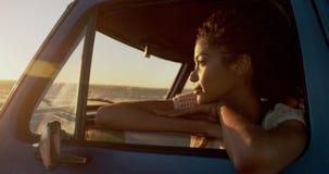 Frau, die auf Fenster des Kleintransporters am Strand 4k sich lehnt stock video footage