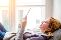 Frau, die auf Fensterbrett mit Smartphone, hörende Musik liegt Stockfotografie
