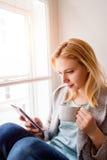 Frau, die auf Fensterbrett mit Smartphone und Kaffee sitzt Lizenzfreies Stockfoto