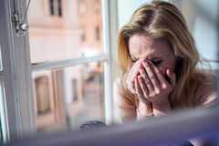 Frau, die auf Fensterbrett, schauend aus dem Fenster heraus sitzt und schreien Lizenzfreie Stockfotos