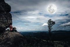 Frau, die auf Flusssteinen, Himmel mit bewölktem und schönem vollem MO sitzt Stockbilder