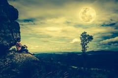 Frau, die auf Flusssteinen, Himmel mit bewölktem und schönem vollem MO sitzt Stockbild