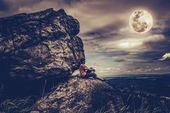 Frau, die auf Flusssteinen, Himmel mit bewölktem und Vollmond sitzt Niedriges KE Stockfotografie