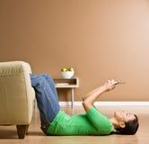 Frau, die auf Fußboden in den Wohnzimmer-Versenden von SMS-Nachrichten legt Stockbilder
