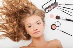 Frau, die auf Fußboden mit Augenschminken und Pinseln legt Lizenzfreie Stockbilder