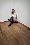 Frau, die auf Fußboden sitzt Lizenzfreie Stockbilder