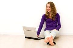 Frau, die auf Fußboden unter Verwendung des Laptops sitzt Stockbild