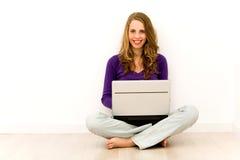 Frau, die auf Fußboden unter Verwendung des Laptops sitzt Lizenzfreies Stockfoto