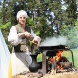 Frau, die auf geöffnetem Feuer kocht Lizenzfreie Stockfotografie