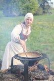 Frau, die auf geöffnetem Feuer kocht Lizenzfreie Stockbilder
