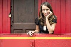 Frau, die auf Geländer im roten Kombüsen-Auto sich lehnt stockfotos